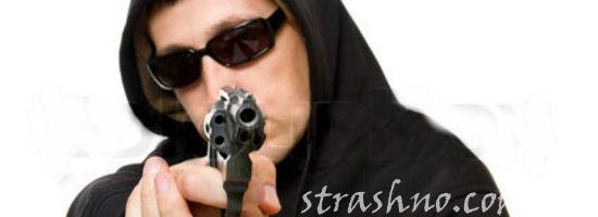 человек в капюшоне с пистолетом