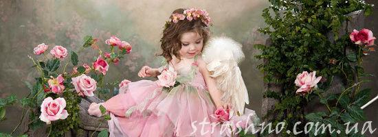 маленькая девочка в розовом платье среди роз