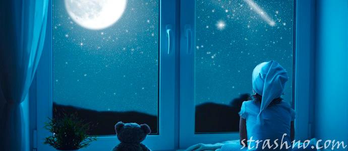 ребенок смотрит в окно на ночное небо